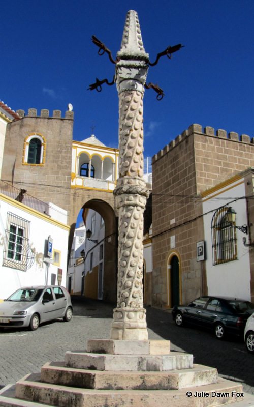 Stone pillory in front of 9th century Islamic city walls, Elvas