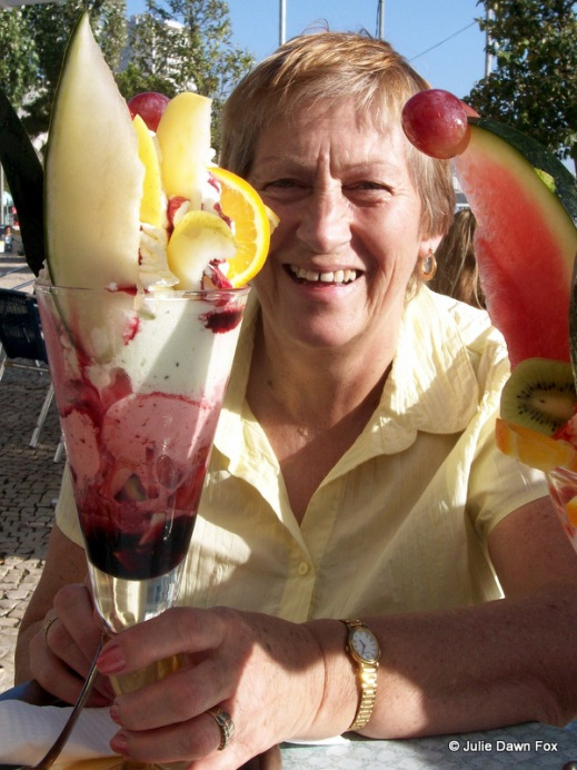 woman smiling between two enormous ice cream sundaes